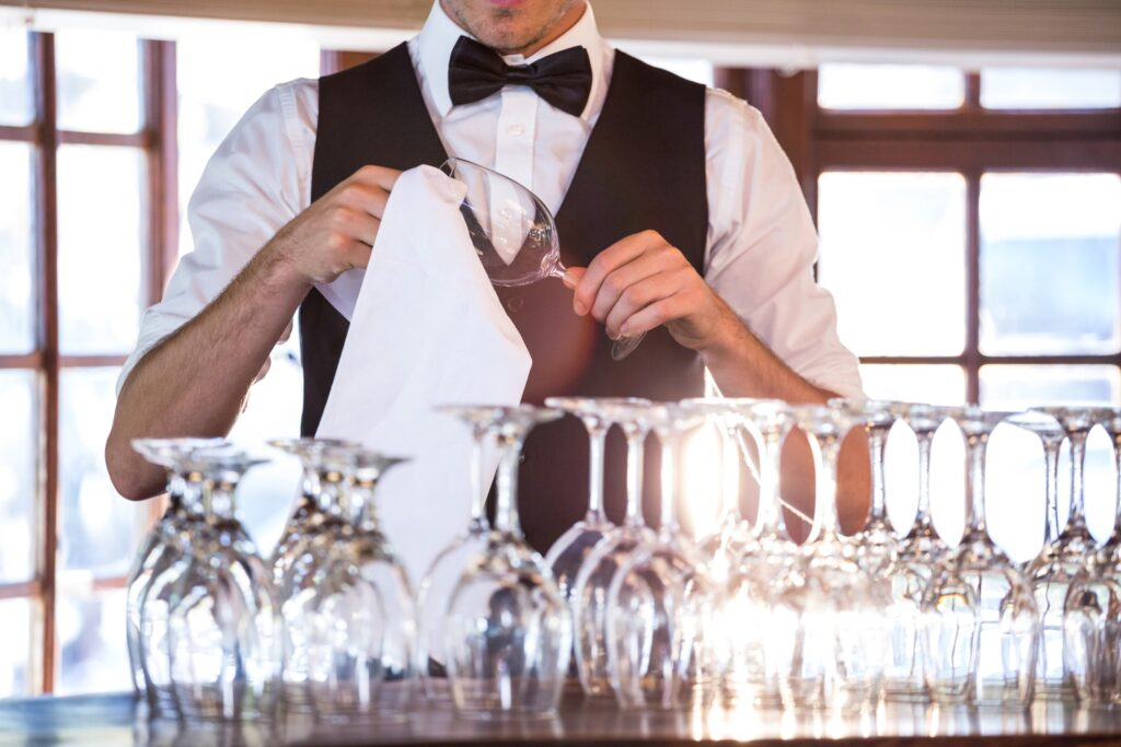 Mid section of bartender cleaning wineglass